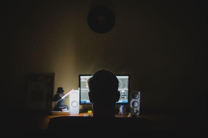Mann sitzt nachts vor dem Monitor