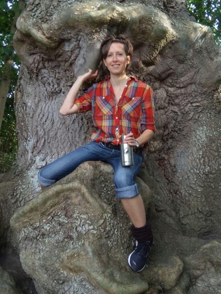 Frau sitzt mit ECOtanka in der Hand auf Baum