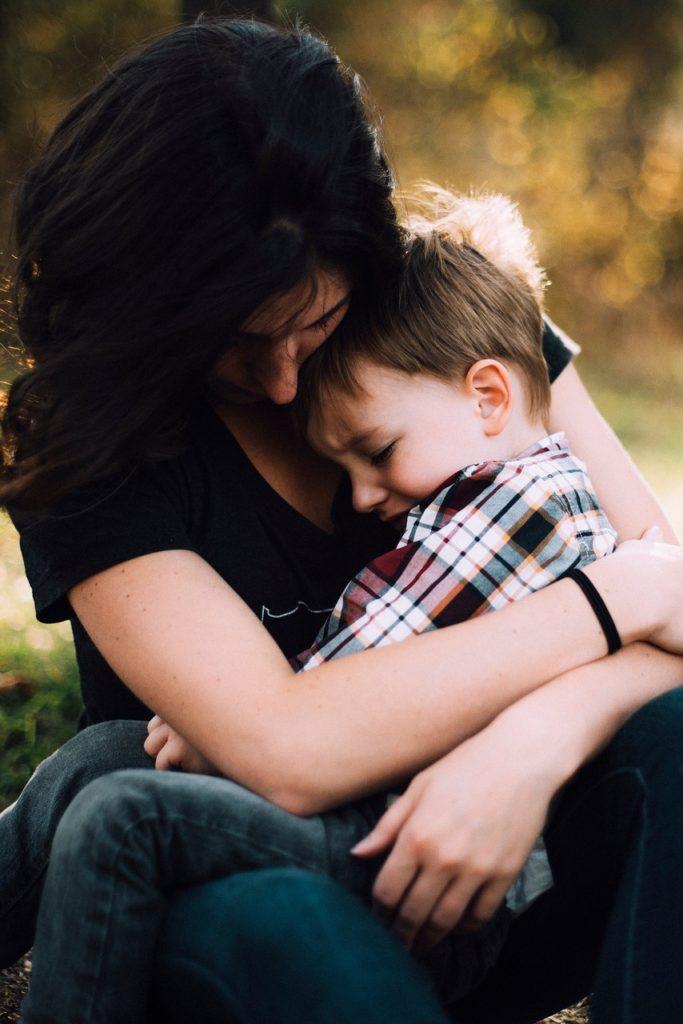 trauriges Kind im Arm der Mutter