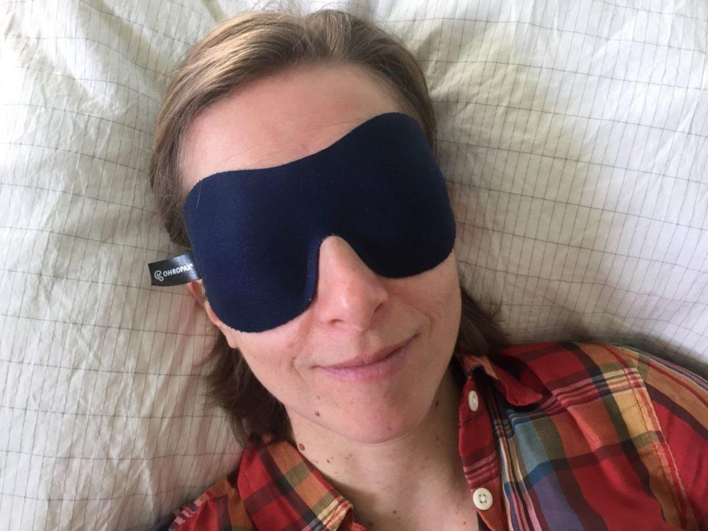 Frau trägt Schlafmaske und liegt auf Erdungskissen